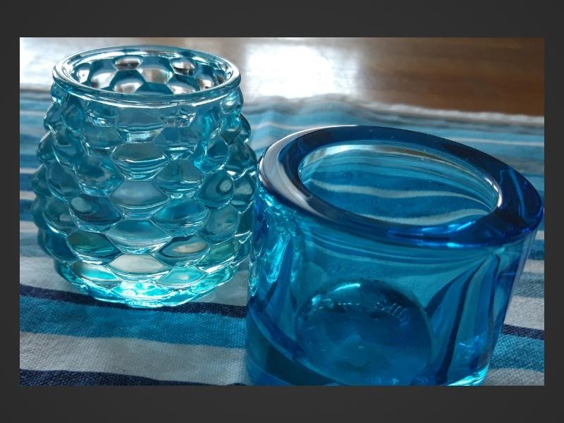 Blå-och vitrandig duk på köksbord av ek, två blå värmeljuslyktor i glas.